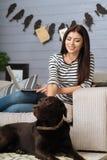 Femme assez heureuse choyant son chien Image stock