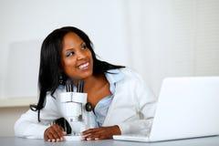 Femme assez jeune à l'aide d'un microscope Photos stock