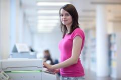 Femme assez jeune à l'aide d'une machine de copie photos stock