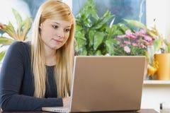 Femme assez jeune à l'aide de l'ordinateur portatif Images libres de droits