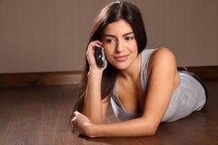 Femme assez jeune à l'aide du téléphone à la maison Photographie stock libre de droits