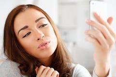 Femme assez jeune à l'aide du téléphone portable photographie stock