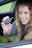 Femme assez jeune affichant hors fonction son véhicule de marque Photo libre de droits