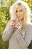 Femme assez jeune avec une cuvette de café à l'extérieur Image stock