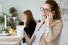 Femme assez jeune d'affaires à l'aide de son téléphone portable tout en buvant du café dans le bureau Image libre de droits