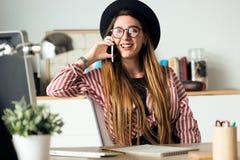 Femme assez jeune d'affaires à l'aide de son téléphone portable tout en buvant du café dans le bureau Images libres de droits