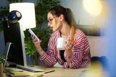 Femme assez jeune d'affaires à l'aide de son téléphone portable tout en buvant du café dans le bureau Photo stock