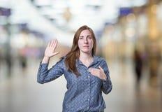 Femme assez jeune d'affaires faisant un serment au-dessus de fond de tache floue image stock