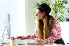 Femme assez jeune d'affaires travaillant avec son ordinateur portable dans le bureau Photographie stock libre de droits