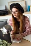 Femme assez jeune d'affaires travaillant avec son ordinateur portable dans le bureau Image libre de droits