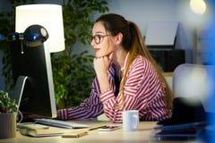 Femme assez jeune d'affaires travaillant avec son ordinateur portable dans le bureau Images libres de droits
