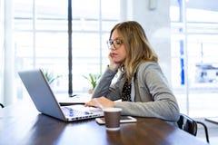 Femme assez jeune d'affaires travaillant avec son ordinateur portable dans le café Image libre de droits