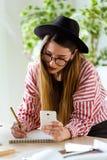 Femme assez jeune d'architecte travaillant à l'des modèles tout en à l'aide de son téléphone portable dans le bureau Images libres de droits