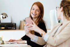 Femme assez jeune des affaires deux à l'aide de son téléphone portable dans le bureau Photos stock