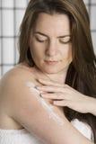 Femme assez jeune mettant sur la lotion d'hydratation Images libres de droits