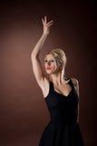 Femme assez jeune posant sur le fond brun Photos libres de droits