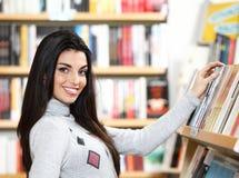 Femme assez jeune recherchant un livre Photos libres de droits