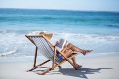 Femme assez mûre lisant un livre se trouvant sur la chaise de plate-forme Image libre de droits