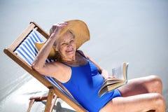 Femme assez mûre lisant un livre se trouvant sur la chaise de plate-forme Photos libres de droits