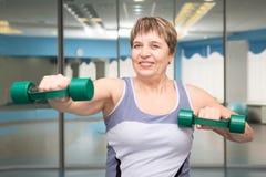 femme assez supérieure s'exerçant dans le gymnase Photo stock