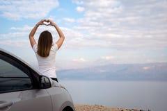 Femme assise sur le capot de moteur d'une voiture lou?e sur un voyage par la route en Isra?l images stock