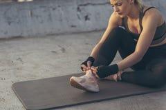 Femme attachant des dentelles avant séance d'entraînement photos libres de droits
