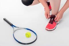 femme attachant des dentelles avant un jeu de tennis Images libres de droits