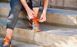 Femme attachant des dentelles des chaussures de course avant se reposer s'exerçant sur des escaliers Images libres de droits