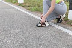 Femme attachant des dentelles de chaussure Coureur femelle de forme physique de sport obtenant lu images stock