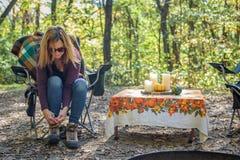 Femme attachant des dentelles sur augmenter des bottes au terrain de camping photo libre de droits