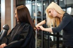 Femme atteignant la coupe de cheveux par le coiffeur féminin le salon de beauté photo stock