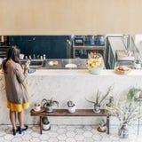 Femme attendant le concept de compteur de barre de café de vue arrière Image libre de droits