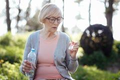 Femme attentive prenant des pilules en parc Photo libre de droits