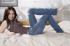 Femme attirant de sourire de jeunes dans des jeans image libre de droits