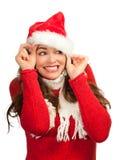 Femme attirant jetant un coup d'oeil à l'extérieur du chapeau de Santa Photographie stock libre de droits