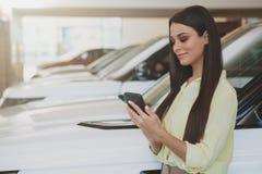 Femme attirante à l'aide de son téléphone intelligent tout en bying la nouvelle voiture image stock