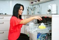 Femme attirante à l'aide du lave-vaisselle photographie stock