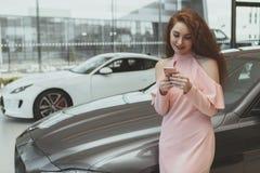 Femme attirante à l'aide du téléphone intelligent au concessionnaire automobile images libres de droits