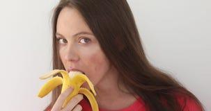 Femme attirante épluchant et mangeant une grande banane banque de vidéos
