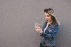 Femme attirante étonnée à l'aide du téléphone intelligent Fond gris, l'espace de copie image stock