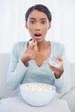 Femme attirante étonnée mangeant du maïs éclaté tout en regardant la TV Images libres de droits