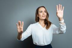 Femme attirante agréable regardant ses mains Image libre de droits