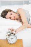 Femme attirante arrêtant le réveil se trouvant sur son lit Photographie stock