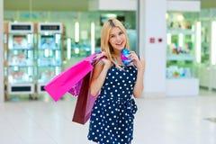 Femme attirante avec des paniers et des cartes de crédit Photographie stock libre de droits