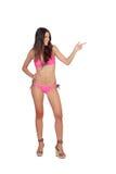 Femme attirante avec des vêtements de bain roses indiquant quelque chose Image libre de droits