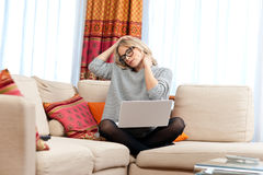 Femme attirante avec l'ordinateur portable ayant la douleur cervicale photographie stock