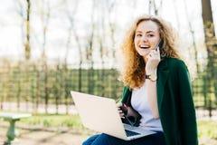 Femme attirante avec la coiffure à la mode se reposant en parc communiquant au-dessus de son téléphone portable utilisant l'ordin photos libres de droits