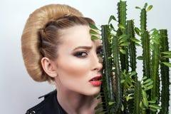 Femme attirante avec la coiffure rassemblée de petit pain posant avec le cactus dans le pot de fleurs d'isolement sur le fond bla photo libre de droits
