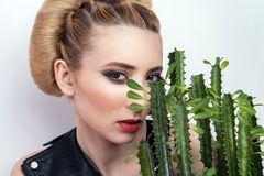 Femme attirante avec la coiffure rassemblée de petit pain posant avec le cactus dans le pot de fleurs d'isolement sur le fond bla images stock