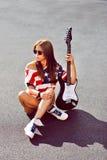 Femme attirante avec le portrait extérieur de mode de guitare électrique Photo stock